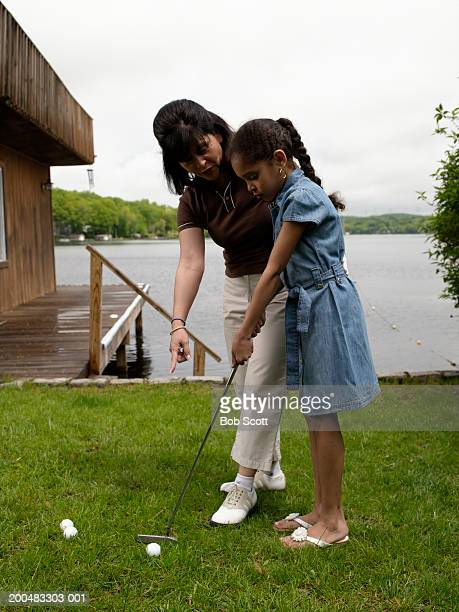 Grandmother teaching granddaughter (8-10) to golf