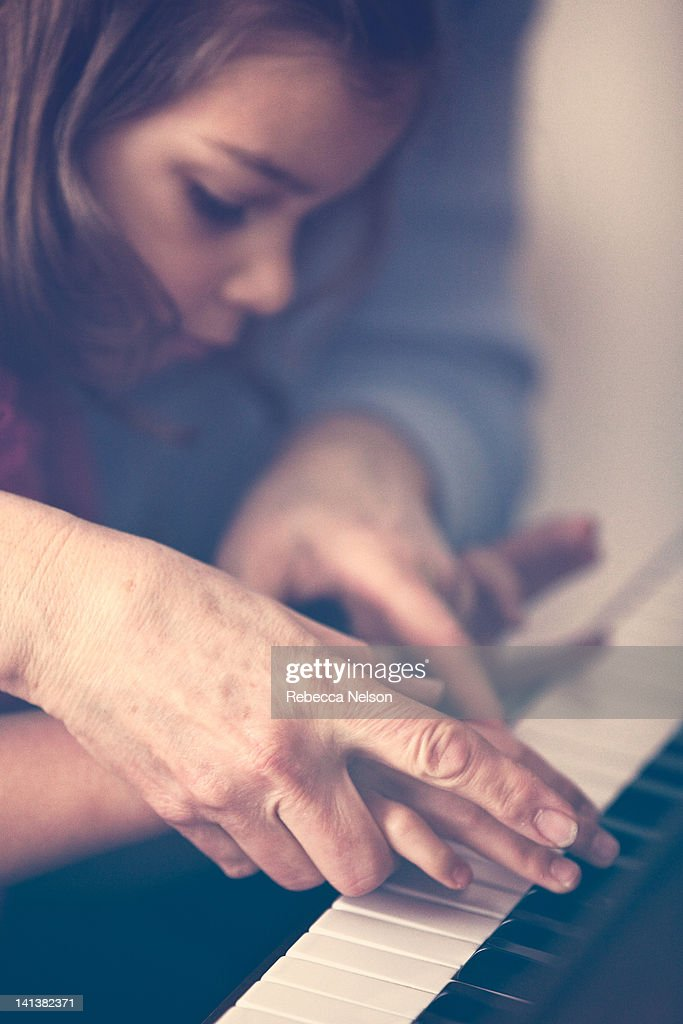Grandmother teaching granddaughter to play piano