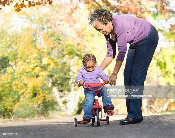 Grandmother teaching granddaughter to ride a bike