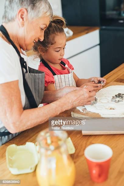 Grandmother teaching her granddaughter to make cookies