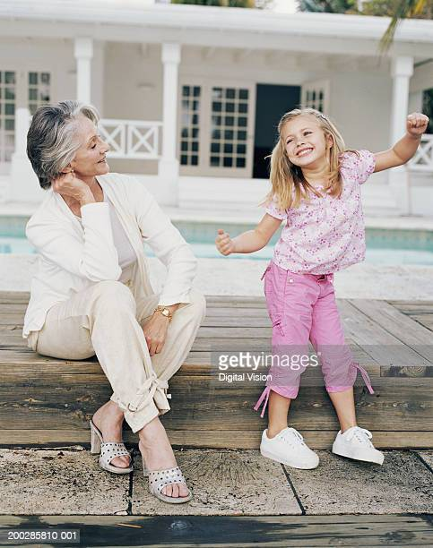 Grandmother watching granddaughter (3-5) dancing by pool, smiling