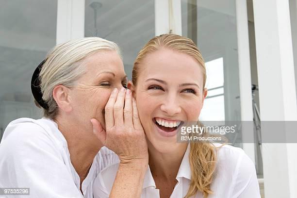 Grandmother whispering daughter
