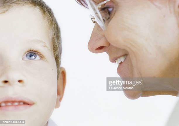 Grandmother whispering into boy's ear