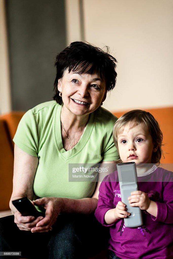 Grandmother with grandchild watching TV