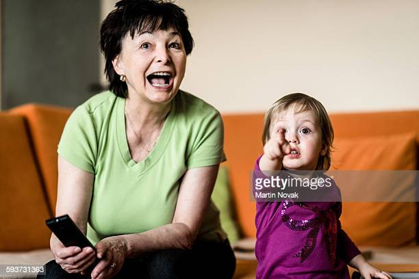 Grandmother with grandchild watching TV