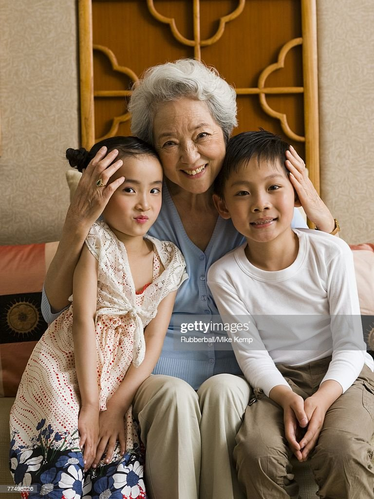 Grandmother with granddaughter and grandson smiling : Stock Photo