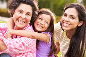 Grandmother With Granddaughter And Mother In Park Smiling To Camera