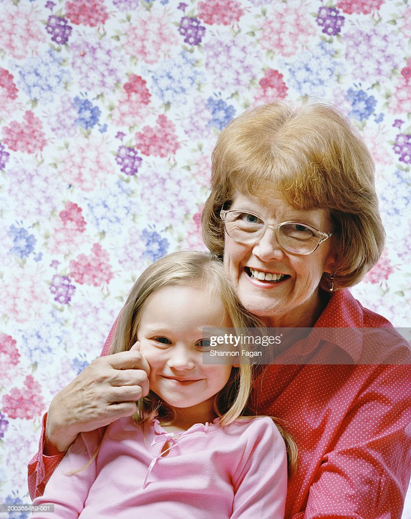Grandmother with granddaughter (4-6) pinching cheek smiling, portrait : Stock Photo
