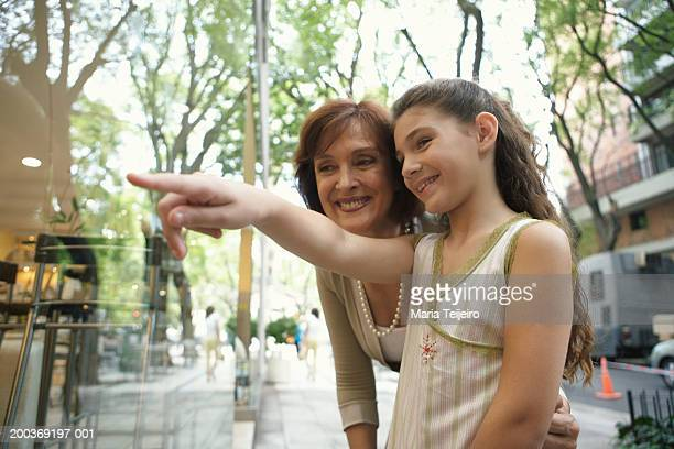 Grandmother with granddaughter (8-10) pointing to shop window, smiling