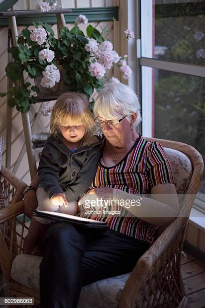 Grandmother with granddaughter using digital tablet
