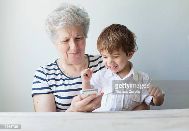 Grandmother with her grandson looking a smartphone