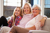 Grandmother With Mother And Adult Daughter Relaxing On Sofa, Smiling To Camera