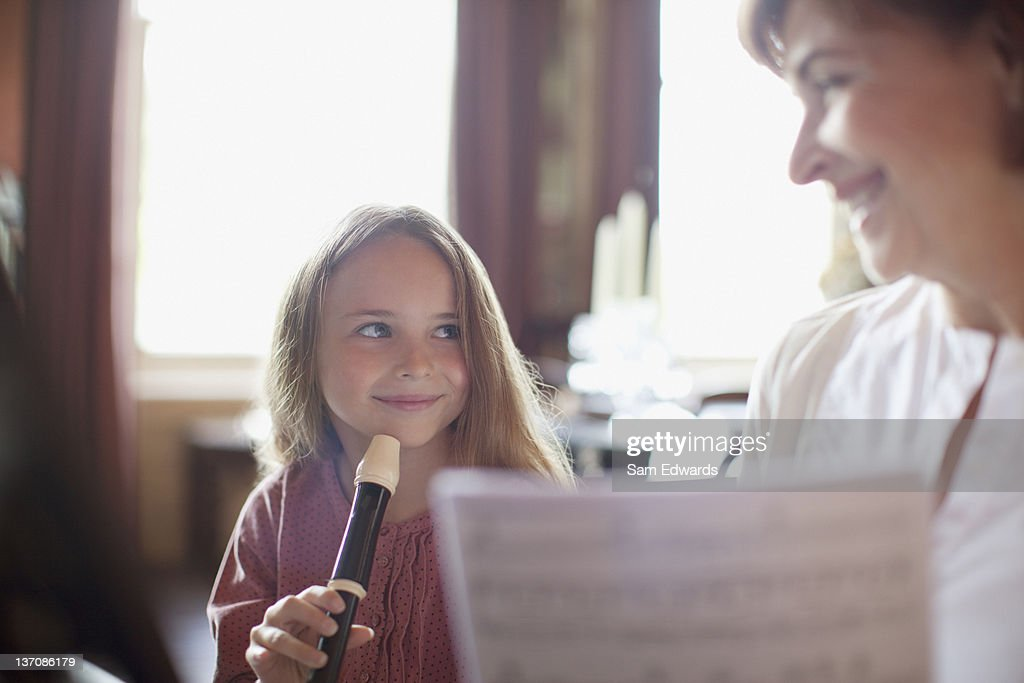 Grandmother with sheet music watching granddaughter practice on recorder : Stock Photo