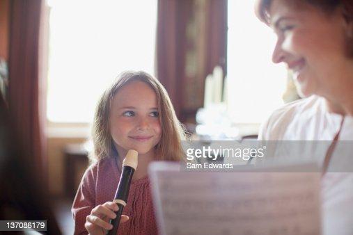 Grandmother with sheet music watching granddaughter practice on recorder : Bildbanksbilder