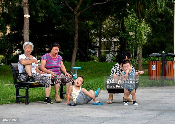 Grandmothers who left their hometowns in other cities to live in Beijing supervise and escort their only grandsons playing in a residential community...