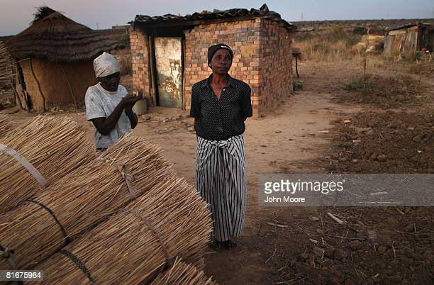 Grandmothers who's children died of AIDS stand in front of their homes in the countryside June 23 2008 outside of Bulawayo Zimbabwe The nation...