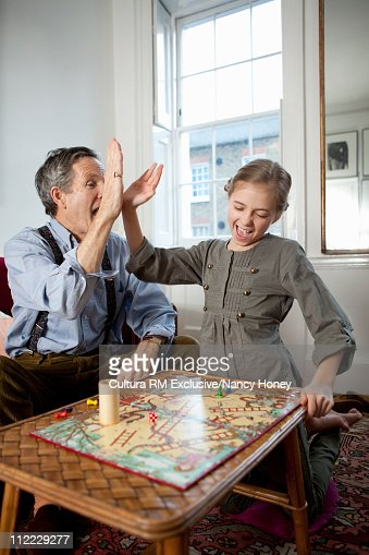 Grandpa and girl playing game and doing a hi-five : Foto de stock