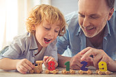 Handsome grandpa and grandson are talking and smiling while playing with toys together at home