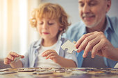 Handsome grandpa and grandson are doing puzzle and smiling while spending time together at home