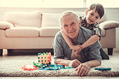 Grandpa and grandson are playing with toys, hugging, looking at camera and smiling while resting together at home