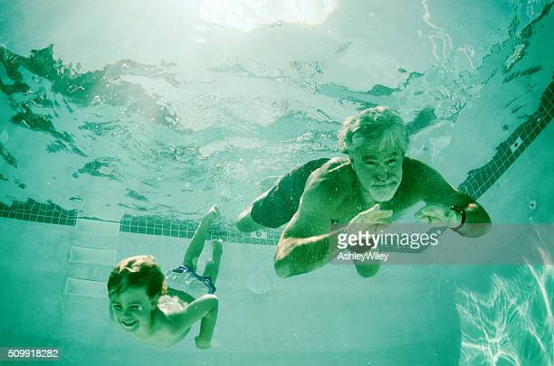 Grandpa and Grandson swimming together underwater in summer