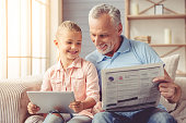 Cute little girl and her handsome grandpa are smiling while sitting on couch at home. Girl is using a tablet while grandpa is reading a newspaper