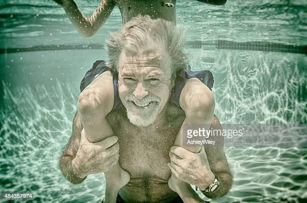 Grandpa juega con su nieto submarina en Piscina en verano
