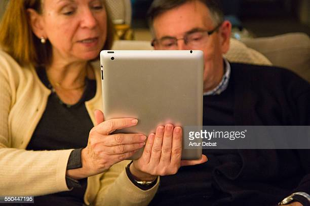 Grandparent couple doing a FaceTime conversation with his granddaughters on iPad tablet