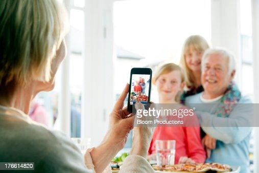 Grandparent taking a picture of her grandchildren