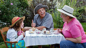 Grandparents and 6 year old granddaughter are sitting at a small table in a garden, having a tea party and making funny faces at each other. Straw hats, china tea cups, cupcakes, and embroidered table