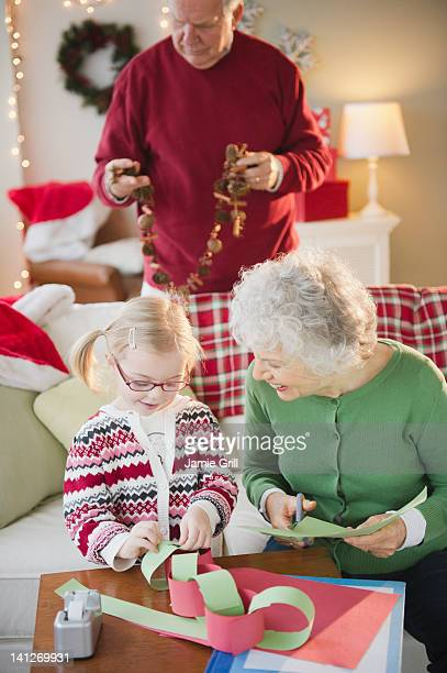 Grandparents and girl making Christmas crafts