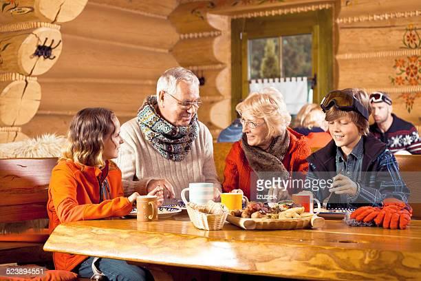 Grands-parents et petits-enfants ayant un déjeuner après le ski