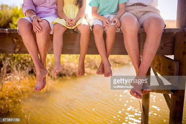Grands-parents et petits-enfants assis ensemble sur un ponton