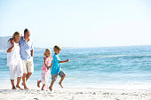 Grandparents and Grandchildren on Holiday Walking Along Beach