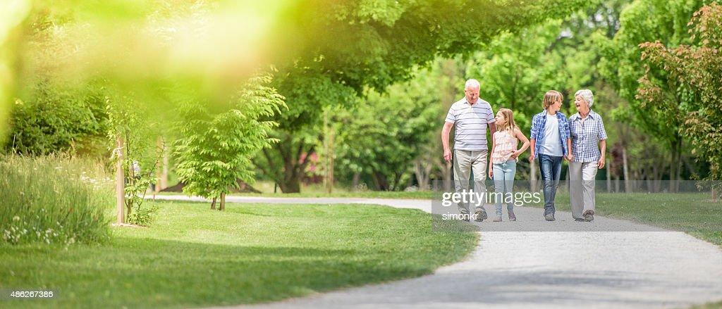 Grands-parents et petits-enfants marchant dans le parc : Photo