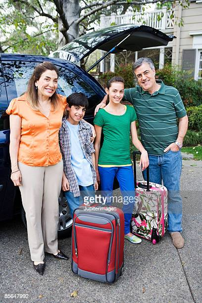 Grandparents and grandchildren with luggage by car