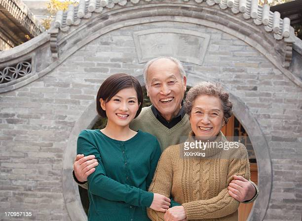 Grandparents and granddaughter in front of round arch, Beijing