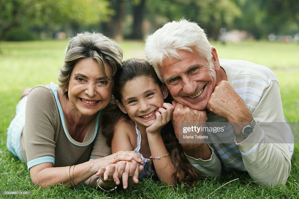 Grandparents and granddaughter (8-10) lying on grass, smiling