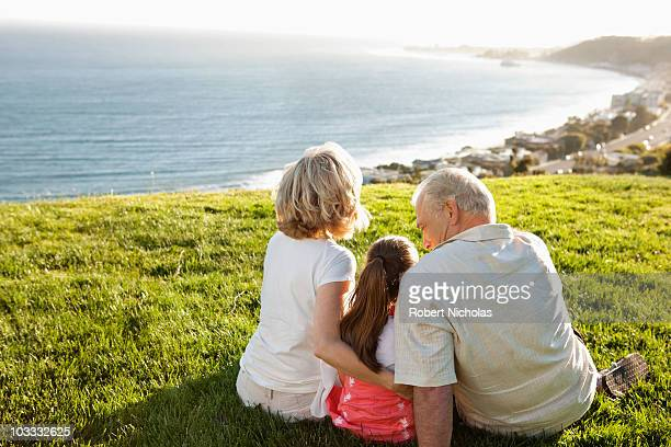 Grandparents and granddaughter sitting in grass overlooking ocean