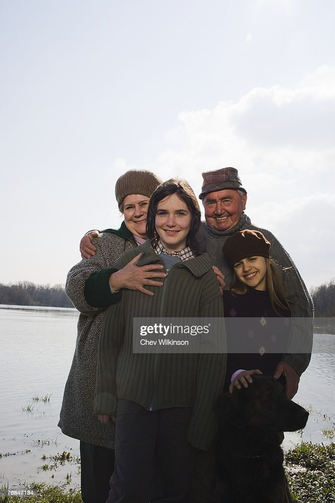 Grandparents and grandson (12-14) and grangdaughter (11-13) standing by river, smiling : Stock Photo
