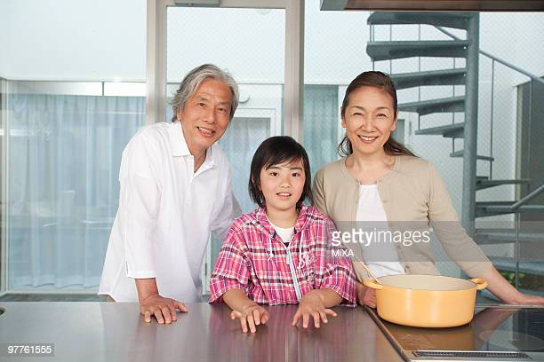 Grandparents and grandson standing in kitchen