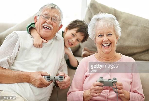 Nonni e bambino che si diverte a giocare videogiochi