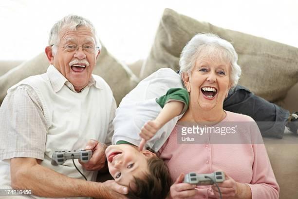 Nonni e piccolo ragazzo avendo divertimento riproduzione di video giochi