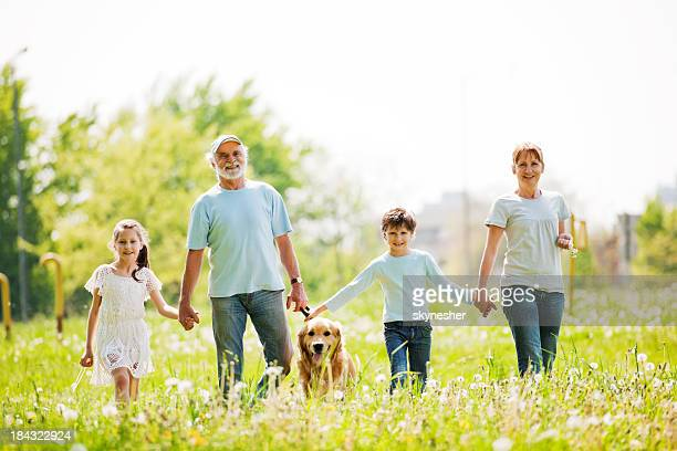 Grandparents and their grandchildren in the park holding hands.