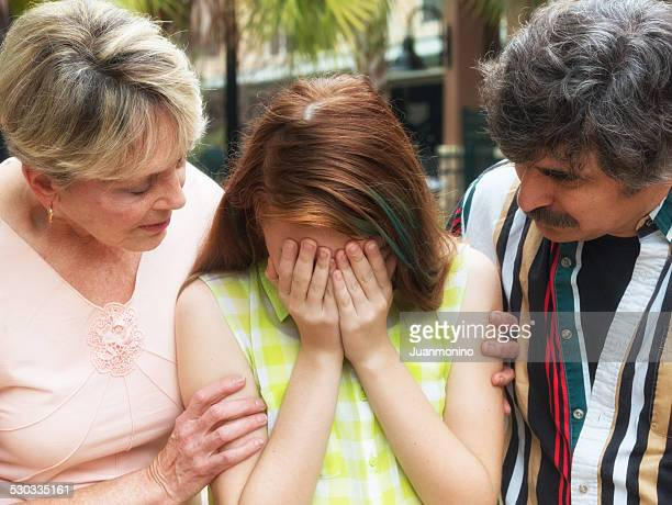 Grandparents consoling their granddaughter