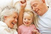 Happy Smilling Grandparents Cuddling Granddaughter In Bed.