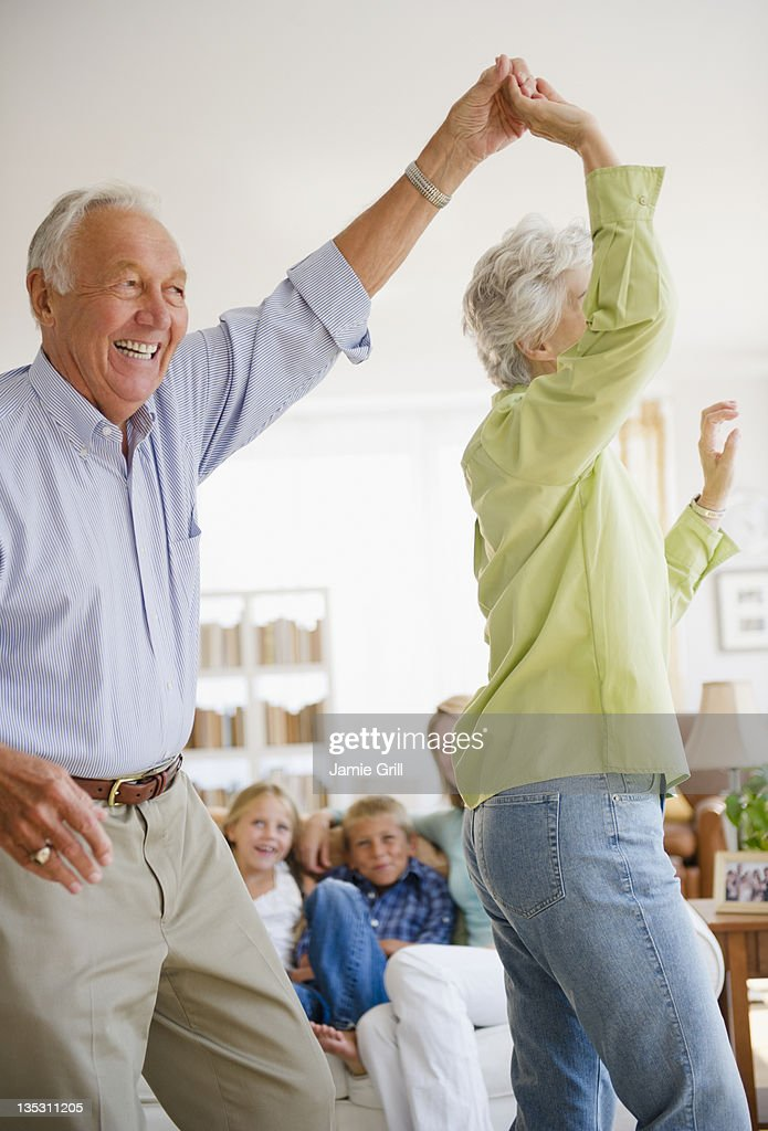 Grandparents dancing in front of family : Stock Photo