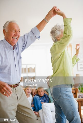 Grandparents dancing in front of family : ストックフォト