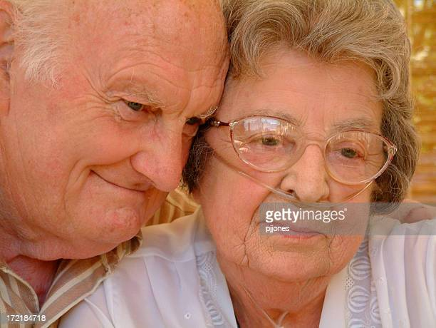 Grandparents giving a soft smile while embracing