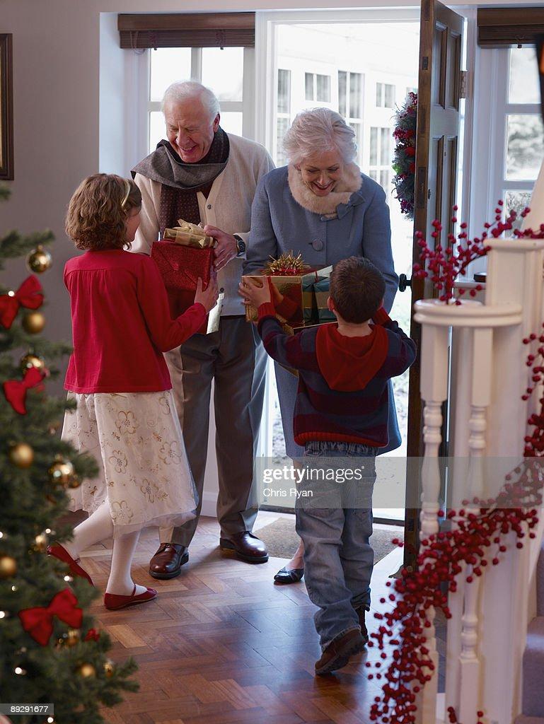 Grandparents giving grandchildren Christmas gifts in doorway